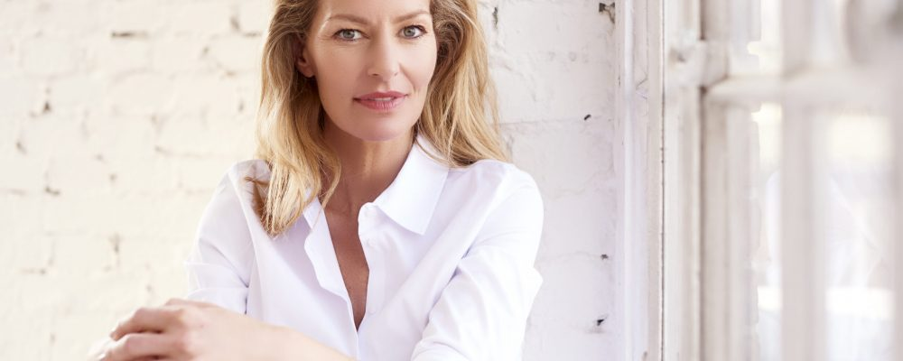 Close-up portrait shot of beautiful blond mature woman wearing white shirt and jeans while relaxing by the window.
